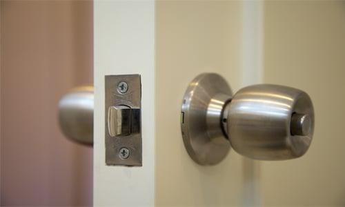open door with door knob, latch, and strike plate